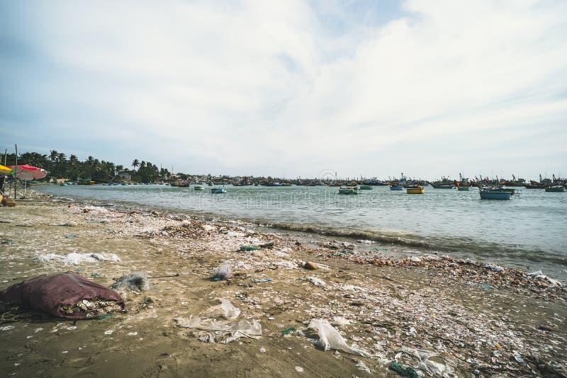 Weergeven op een zandig strand dichtbij aan de visserij van dorp met heel wat huisvuil Verontreiniging van een kustlijn Mui Ne royalty-vrije stock afbeeldingen