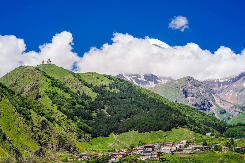 Weergeven op Gergeti-Drievuldigheidskerk - Tsminda Sameba, dichtbij het dorp van Gergeti in Kaukasische bergen, Georgië stock fotografie