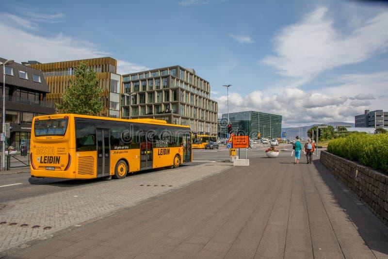 Weergeven op Laekjargata, Harpa-museum op achtergrond, gele het openbare vervoerbus van Besta Leidin in voorgrond, IJsland, Reykj stock afbeelding