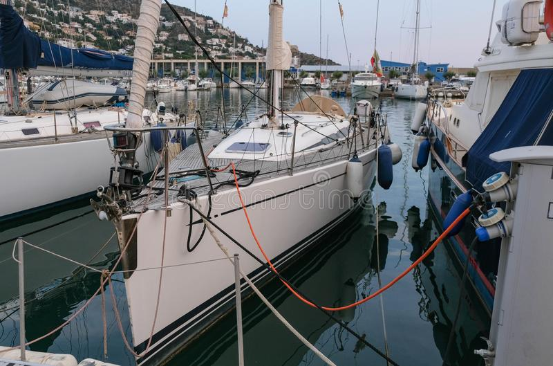 Weergeven op zeilboot die in haven wordt vastgelegd die met de havendiensten wordt verbonden stock foto