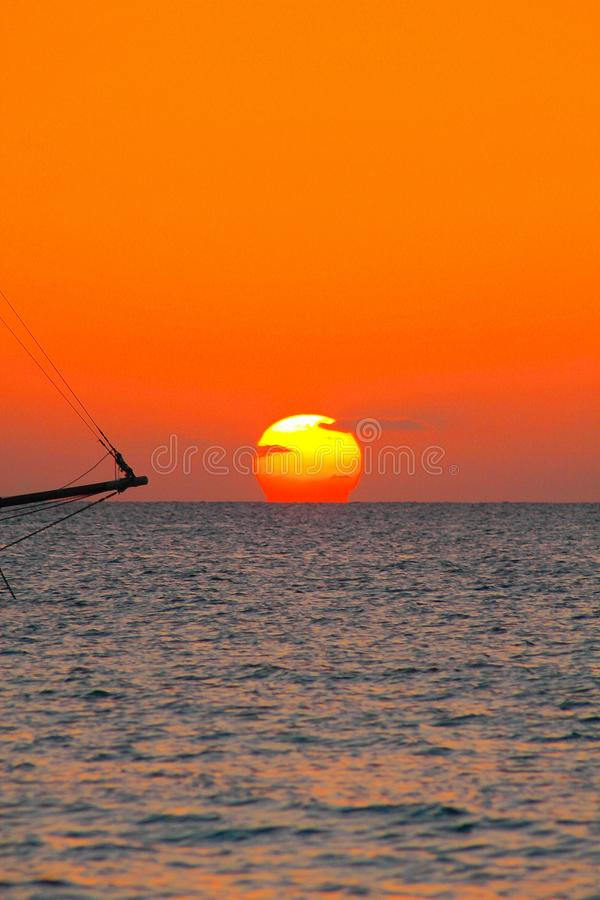 Weergeven op zonsondergang van Caraïbisch strand met oranjerode gloeiende hemel en zwart silhouet van geïsoleerde varende boot stock foto's