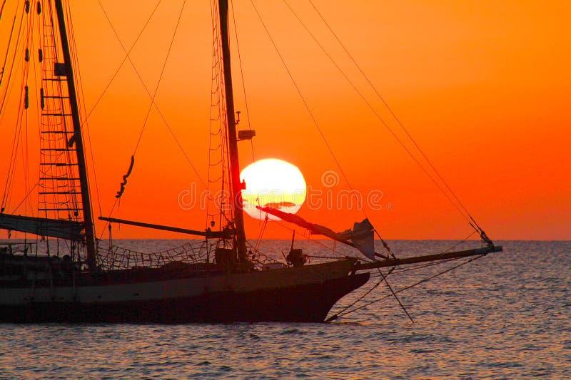 Weergeven op zonsondergang van Caraïbisch strand met oranjerode gloeiende hemel en zwart silhouet van geïsoleerde varende boot stock fotografie