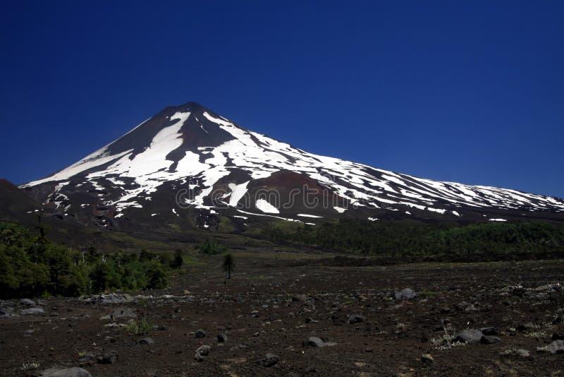 Weergeven over breed gebied van vulkanische lavaas op piek van zwarte Volcano Llaima met vlekken en strepen van sneeuw en ijs royalty-vrije stock afbeeldingen