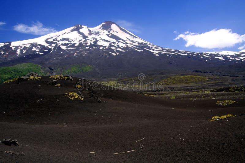 Weergeven over breed gebied van vulkanische lavaas op piek van zwarte Volcano Llaima met vlekken en strepen van sneeuw en ijs royalty-vrije stock fotografie