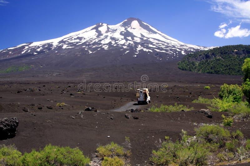 Weergeven over breed gebied van vulkanische lavaas op piek van zwarte Volcano Llaima met vlekken en strepen van sneeuw en ijs stock foto's