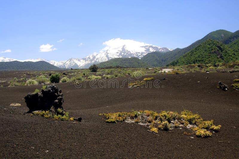 Weergeven over breed gebied van vulkanische lavaas op piek van zwarte Volcano Llaima met vlekken en strepen van sneeuw en ijs stock fotografie