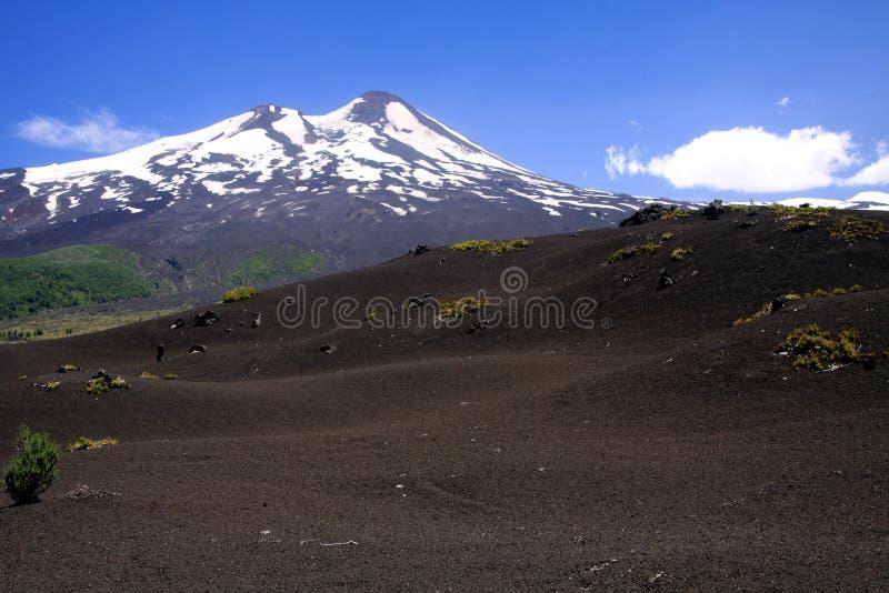 Weergeven over breed gebied van vulkanische lavaas op piek van zwarte Volcano Llaima met vlekken en strepen van sneeuw en ijs stock afbeelding