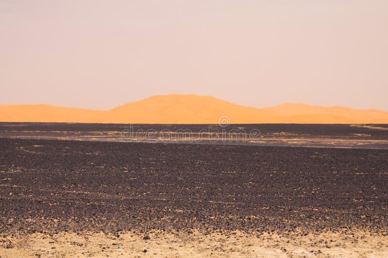 Weergeven over eindeloos gebrand zwart vlak afval steenachtig land op gouden zandduinen en vage sombere hemel, Erg Chebbi, Marokk stock foto's