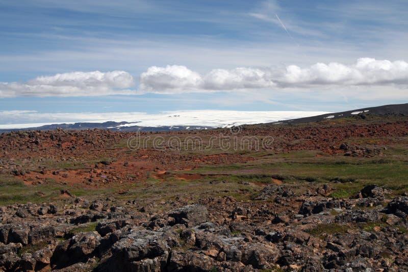Weergeven over onvruchtbare rotsachtige vlakte op bergketen met vlekken van sneeuw, IJsland royalty-vrije stock foto