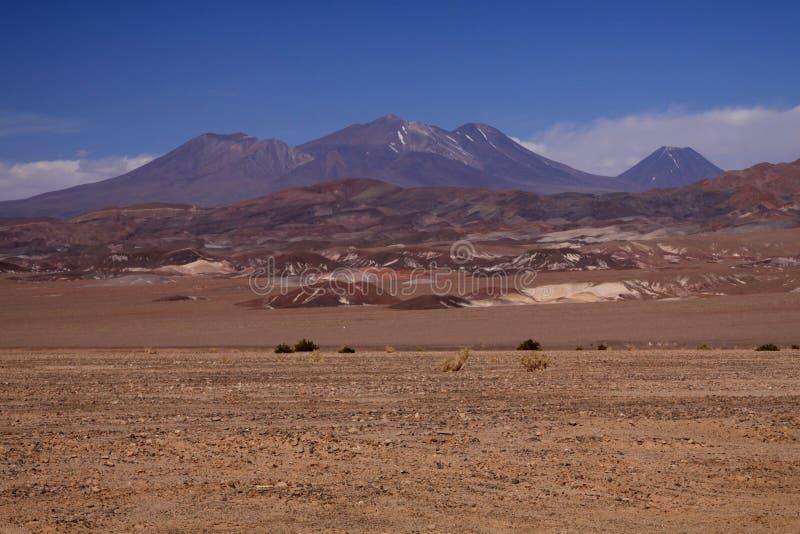 Weergeven over onvruchtbare vlakte op bruine heuvels die met diepe blauwe hemel - Salar Salt vlak dichtbij San Pedro de Atacama t royalty-vrije stock foto's