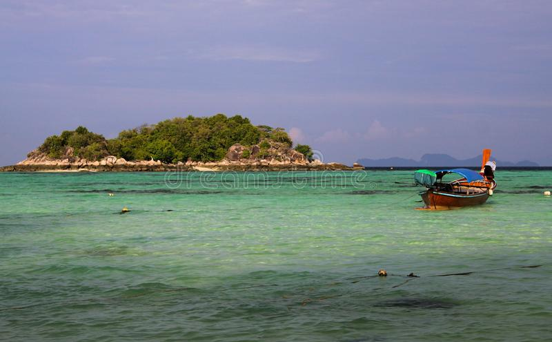 Weergeven over turkooise baai die met blauwe hemel op uiterst klein eiland met lange staartboten tegenover elkaar stellen op Ko L royalty-vrije stock afbeelding