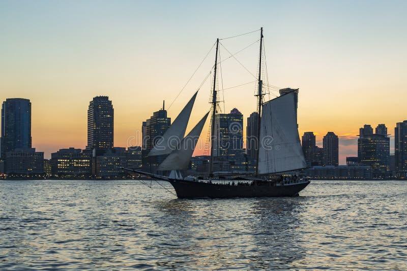 Weergeven tijdens zonsondergang op een oud varend schip op Hudson River en de zon varen die tussen Nieuw sky-line van Jersey City stock fotografie