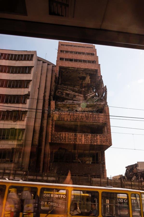 Weergeven van autobusvenster op vernietigd deel van de bouw van de binnenstad in Belgrado na luchtaanvallen in burgeroorlog stock fotografie