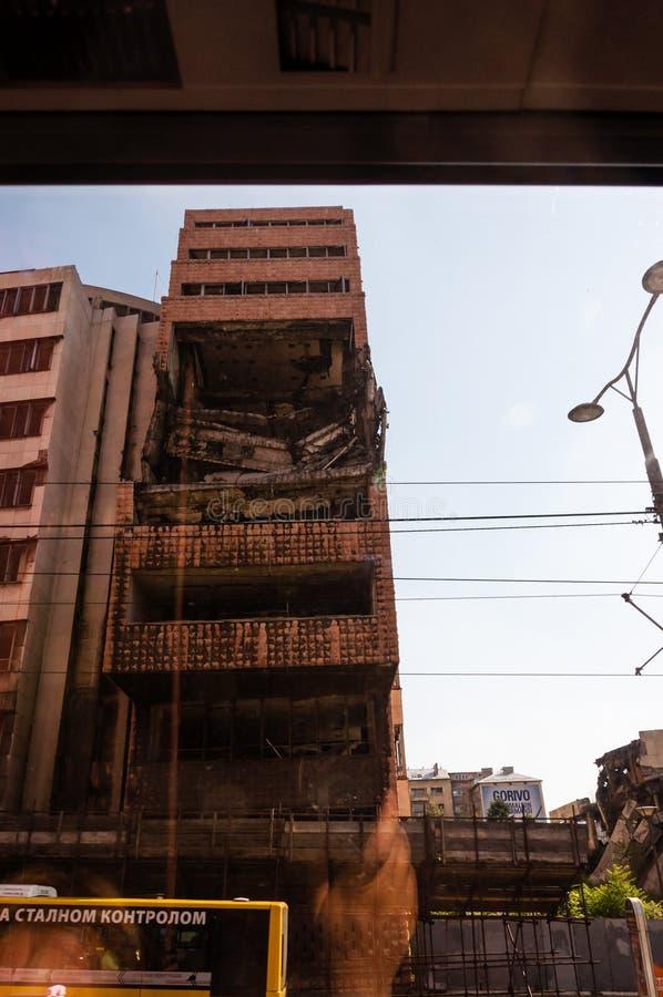 Weergeven van autobusvenster op vernietigd deel van de bouw van de binnenstad in Belgrado na luchtaanvallen in burgeroorlog stock foto's