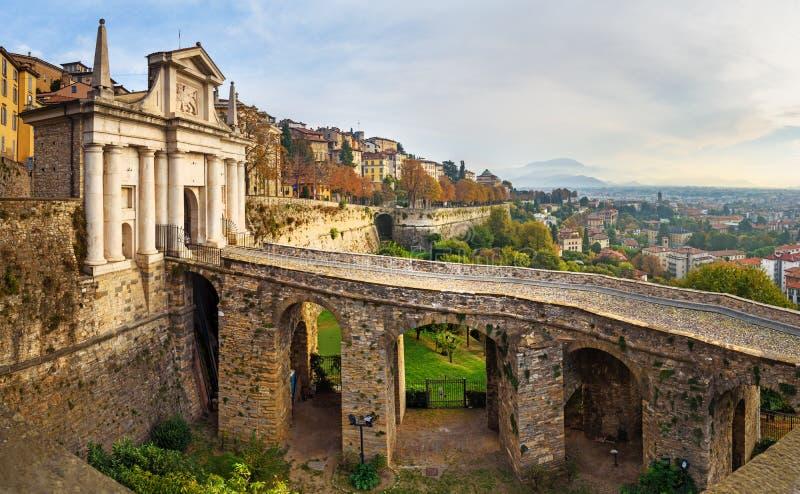 Weergeven van Bergamo met de poort van Porta San Giacomo, het platform van Sant Andrea van Venetiaanse Muren bij ochtend Itali? stock afbeeldingen