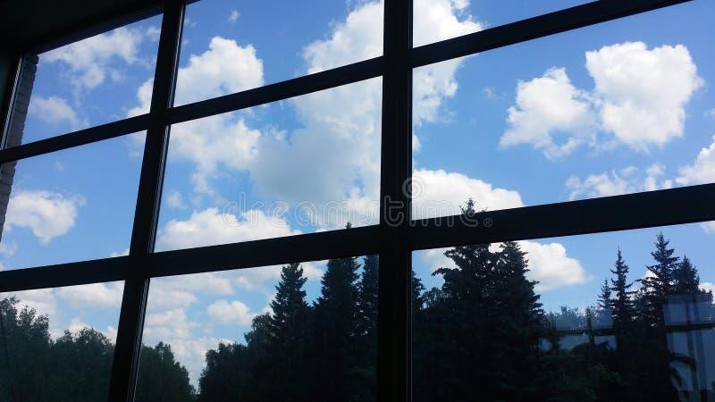 Weergeven van binnenuit van een bureaugebouw door een groot venster bij de hemel met wolken en bij een bos stock foto
