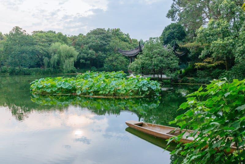 Weergeven van bomen, boot, Chinees paviljoen en bezinningen in water dichtbij het Westenmeer, Hangzhou, China royalty-vrije stock afbeeldingen