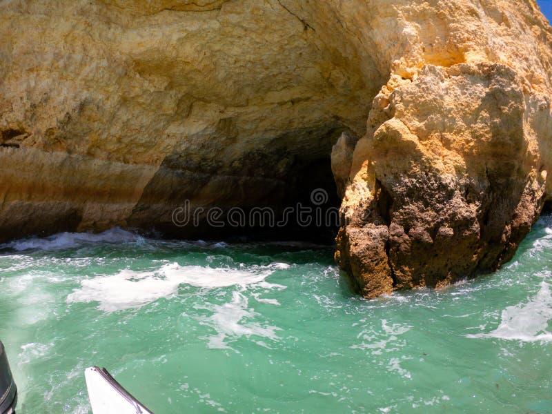 Weergeven van boot op kust en klippen op de Atlantische Oceaan in Algarve, Portugal stock afbeelding