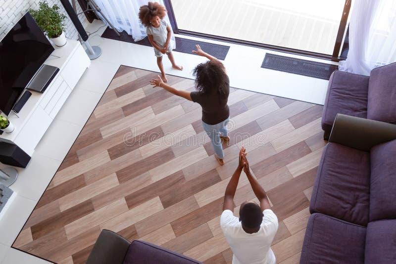 Weergeven van boven het Afrikaanse familie spelen in woonkamer stock foto