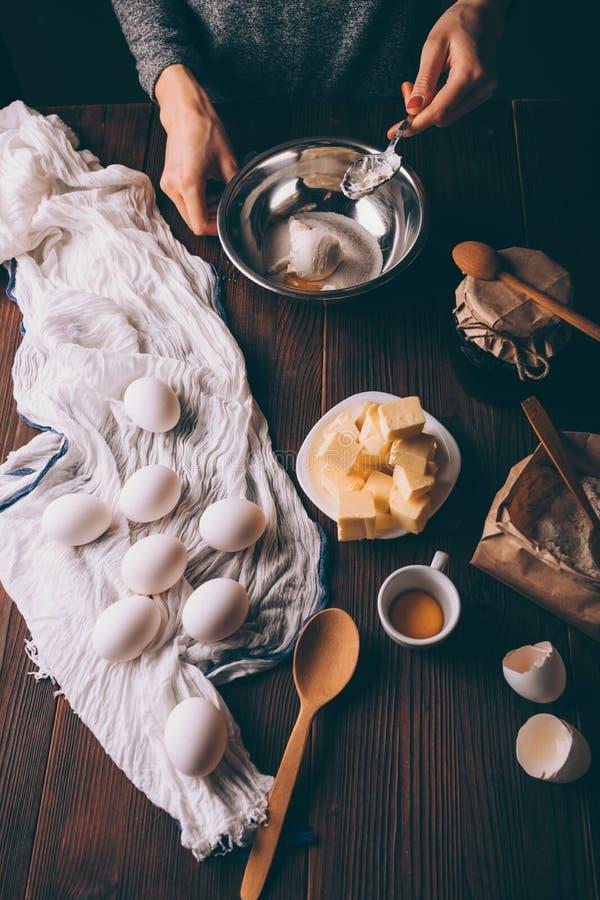 Weergeven van boven jong vrouwen kokend deeg voor pastei die zure room mengen stock afbeeldingen