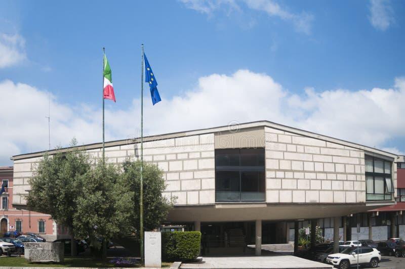 Weergeven van Carrara, Italië: de stadhuis bouw van de Toscaanse stad Carrara met de Italiaanse en Europese vlag stock afbeelding