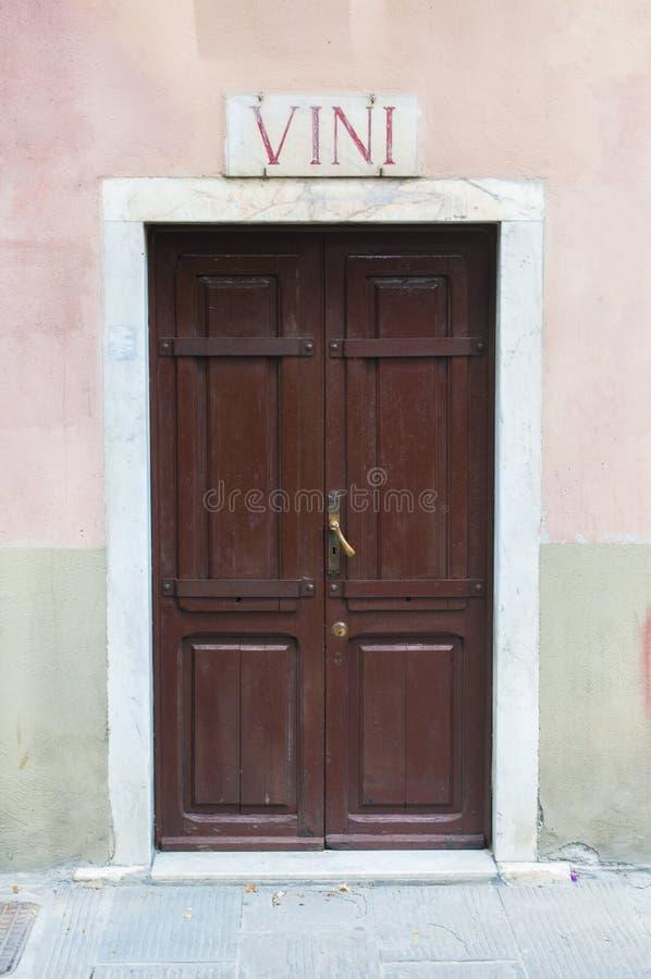 Weergeven van Carrara, Toscanië: oude houten deur van een wijnwinkel met marmeren teken en de tekst: wijn stock foto's