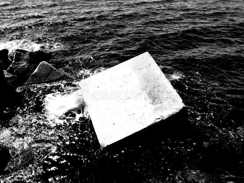 Weergeven van cementblok in het zeewater door de zon wordt verlicht die stock afbeeldingen
