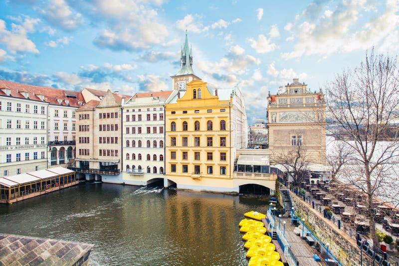 Weergeven van Charles Bridge en de Oude Toren van de Stadsbrug op Vltava-rivier, bewolkte hemel en gele boten, Praag royalty-vrije stock foto