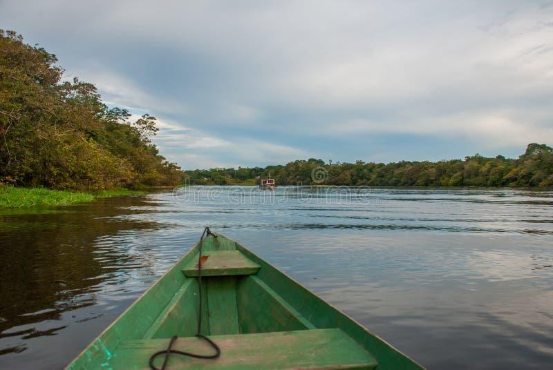 Weergeven van de boot bij de rivier van Amazonië, met een dicht bos op de kust en de blauwe hemel, Anazonas, Brazilië royalty-vrije stock fotografie