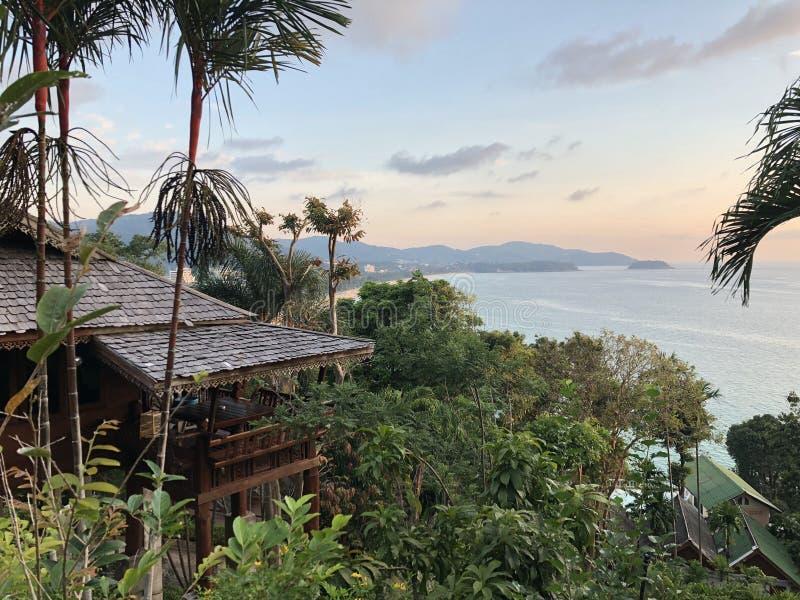 Weergeven van de heuvel aan het wilde strand met weelderige vegetatie en het nationale Thaise huis bij vroege zonsondergang royalty-vrije stock foto