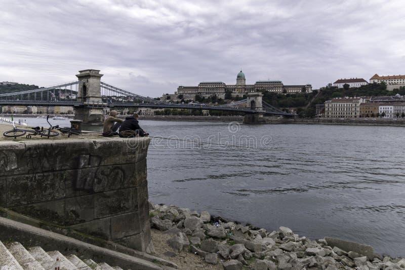 Weergeven van de Kettingsbrug in de middag met Buda Castle met twee fietsers die op de bank van de Donau, Boedapest rusten stock foto's
