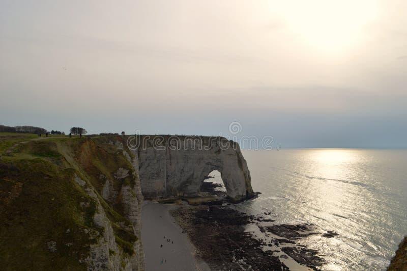 Weergeven van de klippen Etretat van Normandië - zonsondergang aard, oceaan, rots en hemel stock foto