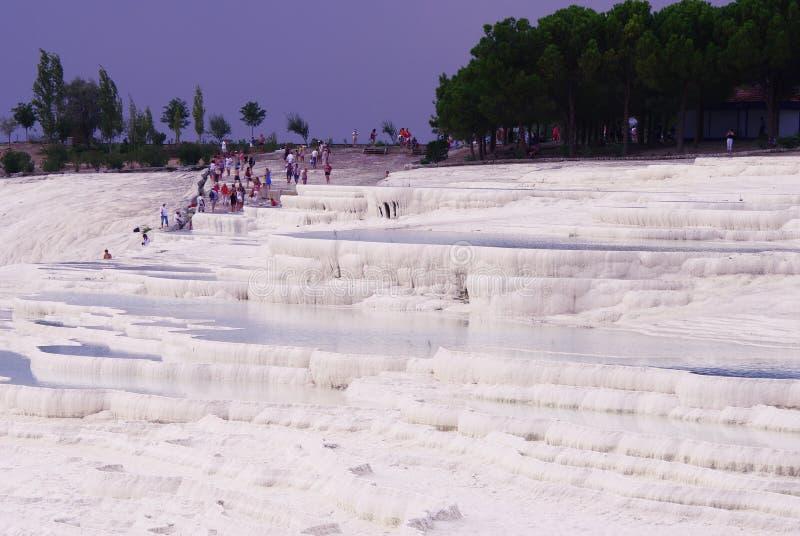 Weergeven van de ongebruikelijke zoute witte berg, de thermische lentes en de toeristen stock afbeeldingen