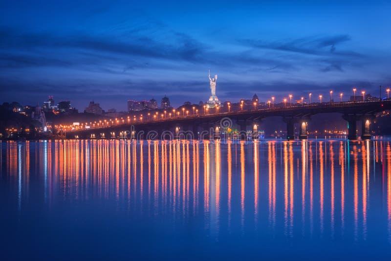 Weergeven van de Paton-brug, het monument van het Vaderland en Dnieper-rivier bij nacht, mooie cityscape, Kiev, de Oekraïne stock afbeelding