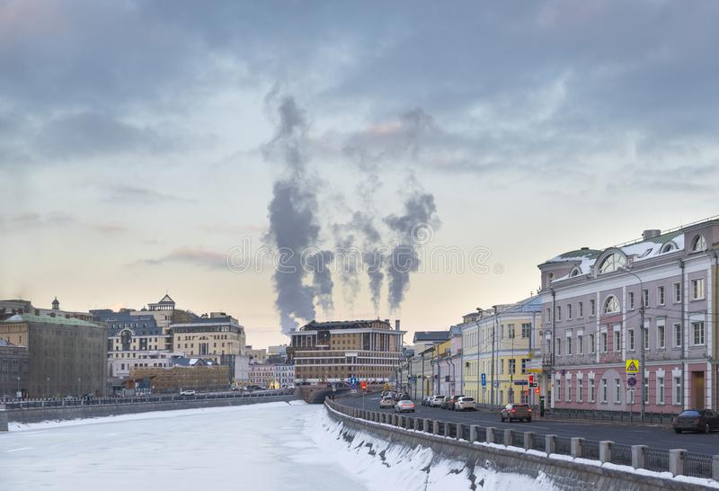 Weergeven van de rivier van Moskou bij zonsondergang, bevroren rivier, gebouwen langs de waterkant, stoompijpen, de hemel met wol stock fotografie