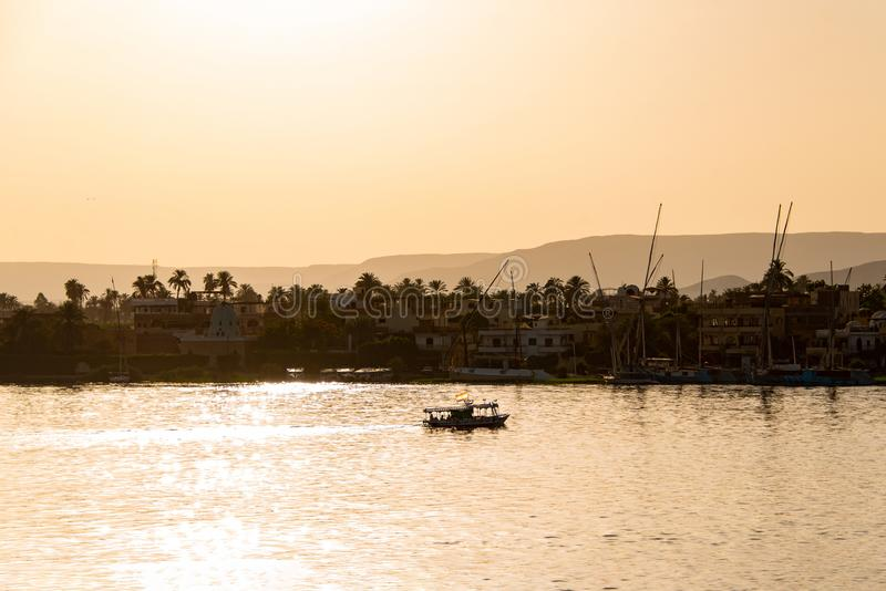 Weergeven van de rivier van Nijl met zeilboten bij gouden kleurrijke zonsondergang in Luxor, Egypte stock foto's