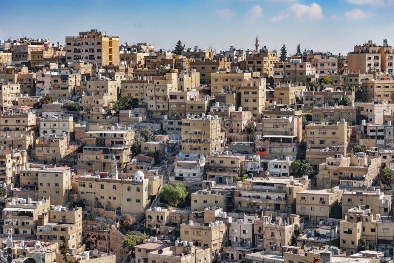 Weergeven van de roze vierkante blokken van de stad van Amman, van een hoog standpunt, op de achtergrond een duidelijke blauwe he stock afbeelding