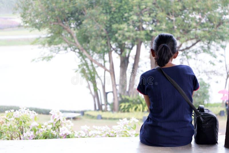 Weergeven van de rug van een jonge vrouwenzitting op een vooruitzicht royalty-vrije stock foto