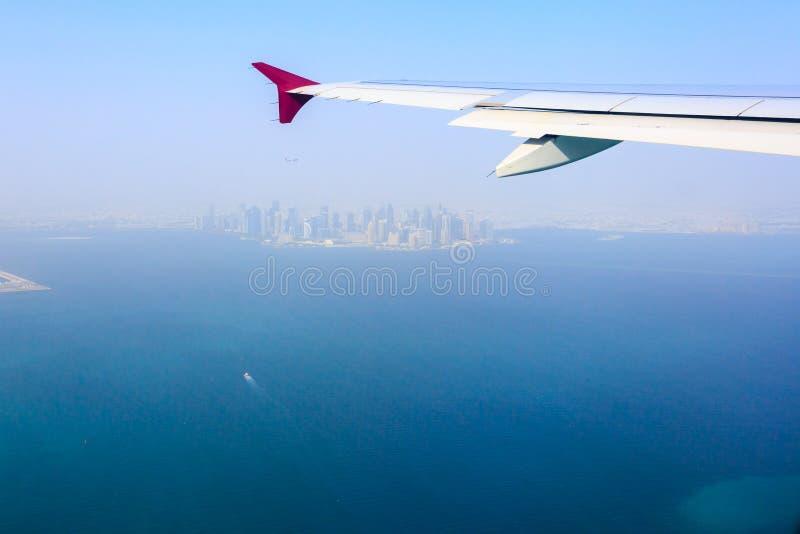 Weergeven van de stad van Doha, Qatar van de vliegtuigpatrijspoort Vliegtuigvliegen over de wolkenkrabbers reis concept stock foto's