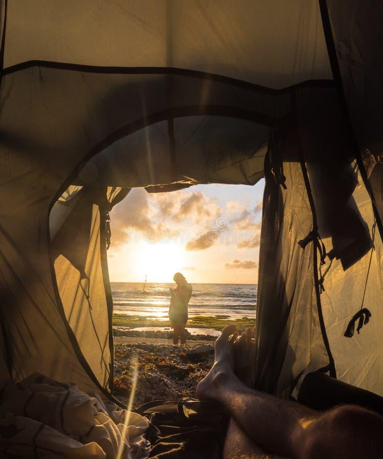 Weergeven van de toeristentent aan het dageraadoverzees De kerel ligt in een tent Het meisje op de achtergrond van het zonsonderg stock afbeeldingen
