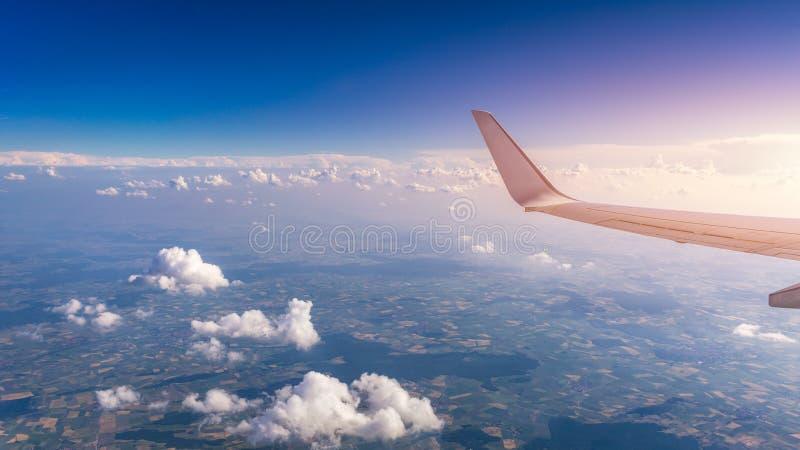 Weergeven van de vleugel van een vliegtuig die boven de wolken bij hoge hoogte onder een blauwe hemel van het passagiersvenster v royalty-vrije stock foto