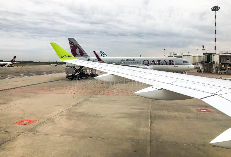 Weergeven van de vliegtuigen van Qatar en vleugel van AirBaltic-vliegtuig in de Internationale Luchthaven Milaan-Malpensa royalty-vrije stock afbeeldingen