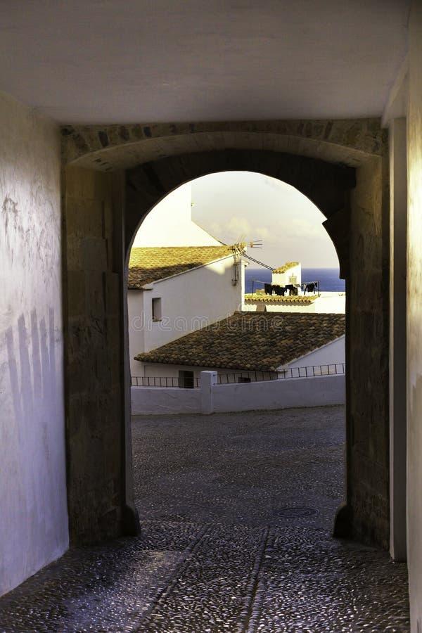 Weergeven van de witte huizen met een betegeld dak door de boog in de oude stad van Altea, Spanje op een hete zonnige dag royalty-vrije stock foto
