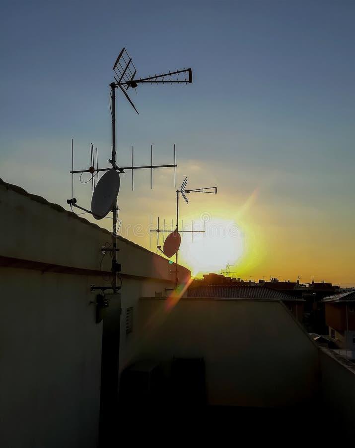 Weergeven van de zon die van een terras met verscheidene satellietschotels plaatsen royalty-vrije stock foto