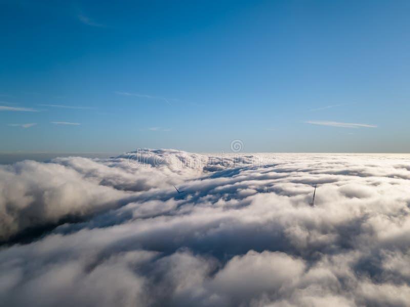 Weergeven van een hommel boven de mist, windturbines met mist en blauwe hemel stock afbeelding
