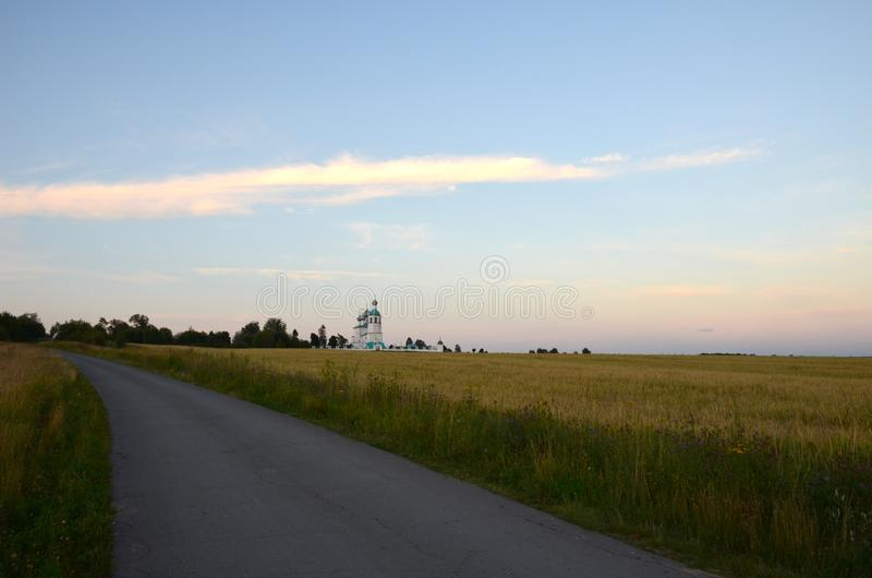 Weergeven van een kerk en een kerkhof in de afstand achter de weg, over het gebied, vóór zonsondergang royalty-vrije stock afbeelding
