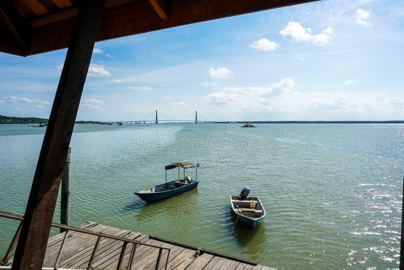 Weergeven van een mens door de pier die kabel van zijn boot beveiligen aan een houten pier Mening van een houten pier royalty-vrije stock afbeeldingen