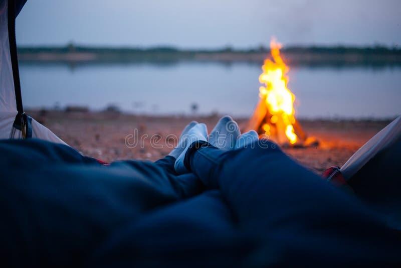 Weergeven van een tent met een brand en een rivier royalty-vrije stock afbeeldingen