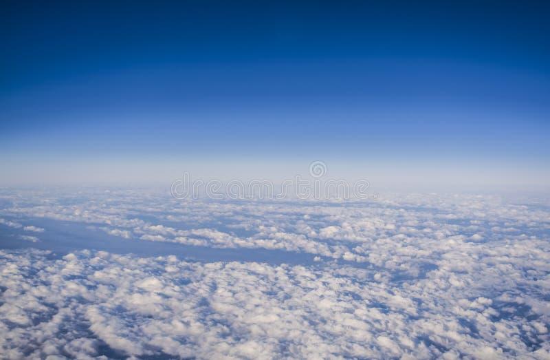 Weergeven van een vliegtuigvenster op wolken en blauwe duidelijke hemel en de aarde van hoogte Mooie mening van lucht van bergen royalty-vrije stock foto