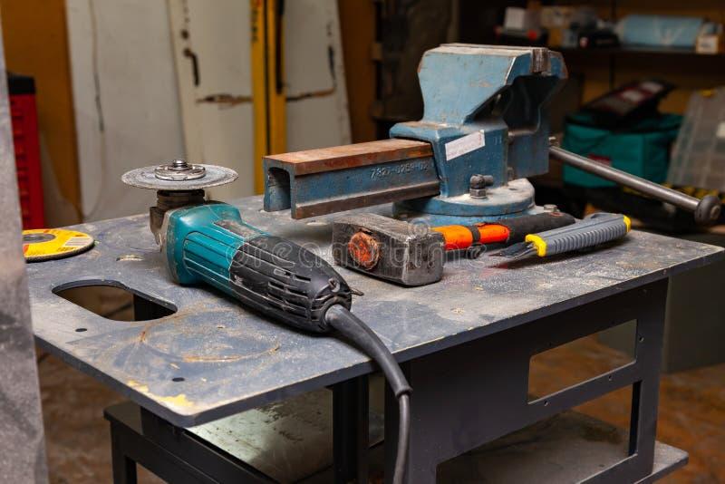 Weergeven van een werkbank met een reeks hulpmiddelen die uit een grote zware bankschroef, een hoekmolen, een schroevedraaier, ee royalty-vrije stock fotografie